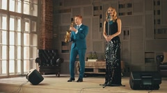 Jazz vocalist in glare dress and saxophonist in blue suit perform on stage Stock Footage