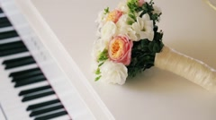 Colorful wedding bouquet on a white piano. Accessories of bride, pink roses Stock Footage