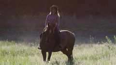 Girl in hat riding a horse at sunset in slowmotion Stock Footage