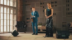 Jazz vocalist in glare dress and saxophonist in blue suit on stage. Dance. Sing Stock Footage