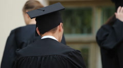 Cheerful young people in academic gowns and caps ready for graduation ceremony Stock Footage