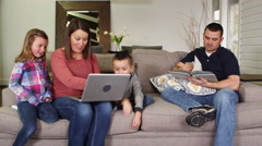 Family using laptop and reading book in living room Stock Footage