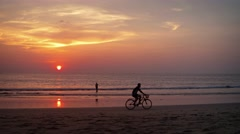Tourist Riding Bicycle on the Beach at Sunset. Video 4k Stock Footage