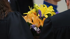 Happy students with bunches of flowers receiving congratulations on graduation Stock Footage