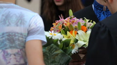 Friends congratulating happy students on graduation with bunches of nice flowers Stock Footage