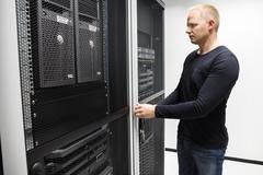 Computer Engineer Opening Server Rack Door In Data Center Stock Photos