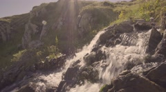 Beautiful waterfall in the swiss alps with sun beams 4K UHD Stock Footage