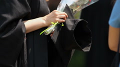Female university graduate holding academic hat and bunch of flowers in hands Stock Footage