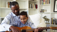 African American father teaching son to play guitar Stock Footage