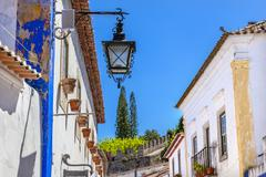 Narrow White Street 11th Century Castle Wall  Lamp Obidos Portugal Stock Photos