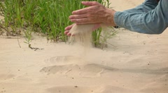 Man Picks up Double Handful of Sand on the Beach. Video 4k Stock Footage