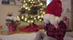 Little Boy Covers His Eyes With Santa Hat, Then Shakes It Off, Funny Stock Footage