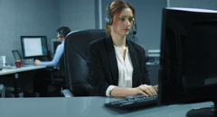 4K: Two female callcenter agents are working at her computer with a Headset. Stock Footage