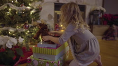 Little Girl Places A Stuffed Animal On Pile Of Presents Under Christmas Tree Stock Footage