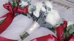 A wedding bouquet of beautiful white peons is lying on the white veil material Stock Footage