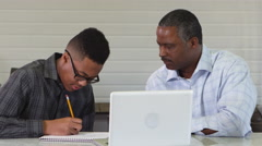 African American father tutoring son in homework Stock Footage