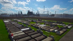 An aerial over a Louisiana cemetery reveals a huge chemical factory refinery in Stock Footage