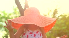 Playful cute little girl wearing a big hat and having fun in summer garden Stock Footage