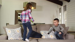 Slow motion brother and sister jumping on the sofa in the living room Stock Footage