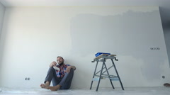 Tired, overworked man taking break from painting wall at his new home Stock Footage