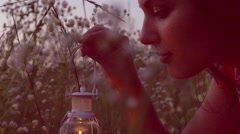 Beautiful girl with lantern finding magic lights in grass at night. Stock Footage