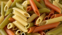 Colorful raw pasta rotating on a white plate. Seamless loopable. Prores 4K Stock Footage