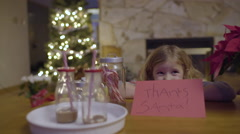 Little Girl Hides Behind Her Thank You Note To Santa, She Peeks Out And Smiles Stock Footage