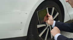 CLOSE UP: Insurance inspector estimating damages on Tesla Model S with tablet Stock Footage