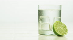 Slice of lime in a carbonated drink in a clear glass Stock Footage