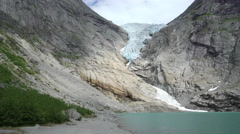 Glacier and lake in the mountains - Briksdale glacier, wild scenery, Norway Stock Footage