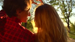 Young couple sitting on the bench park and making heart gesture together. Stock Footage