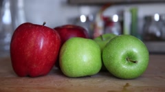 Green and red apples on kitchen table, slider shot Stock Footage