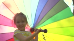 Happy little girl playing with colorful umbrella in sunny park. Smiling child. Stock Footage