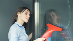 Young woman cleaning window at home Stock Footage