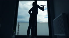 Silhouette of young woman cleaning window at home Stock Footage