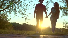 Happy joyful young couple walking in a park together over sunset Stock Footage