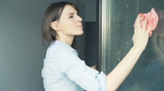 Young woman with detergent cleaning window at home Stock Footage