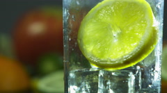 Pouring water into a glass with a lemon Stock Footage