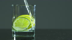 Water filling up a glass with a slice of lime and lemon Stock Footage