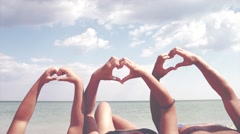 Happy young family making heart shape with their hands over sea background Stock Footage
