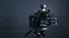 Professional digital video camera, camcoder isolated on black background in tv Stock Footage