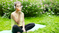 Girl eating apple and listening music while sitting on exercising mat Stock Footage