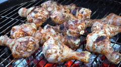 Cooking chicken legs on grill net at round barbeque Stock Footage