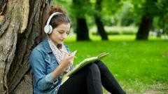 Girl listening music on headphones and writing in notebook in the park Stock Footage