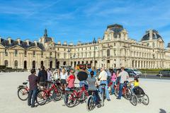 PARIS, FRANCE - APRIL 6, 2011: Group of cycling tourists looking at the Louvr Stock Photos