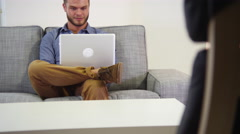 Portrait of man using laptop in living room Stock Footage