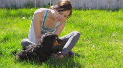 Slow motion woman playing with small black dog Stock Footage