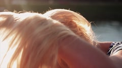 Beautiful young caucasian girl playing with her blond hair on sunset in front of Stock Footage