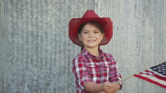 Young cowgirl waving american flag Stock Footage