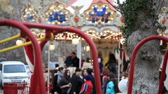 Foreground - children swinging on a swing, background - carousel Stock Footage